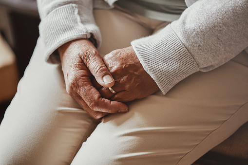 Cropped shot of a senior woman sitting with her hands clasped in a nursing home.