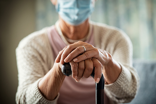 Close up of senior woman's hands holding walking stick and wearing face protective mask in nursing home during covid19 pandemic.